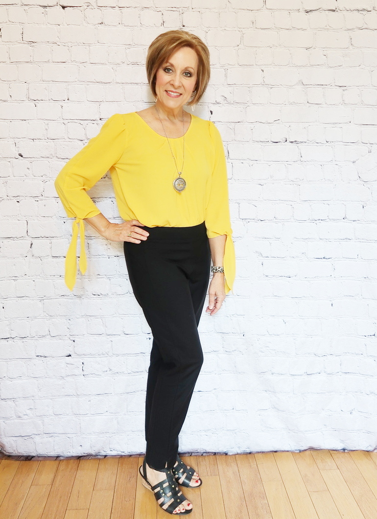 50 With Flair, Mustard Blouse with Tailored Black Pants, Silver Reading Pendant